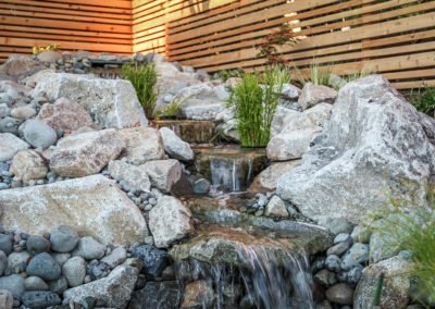 Water feature in landscape constructed of rocks and boulders with plants and wood fencing