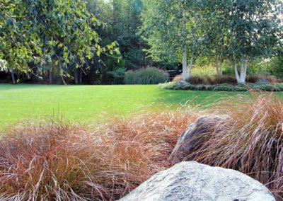 Landscaping and lawn with plants and rocks. Landscape designed by Emily Russell, ASLA